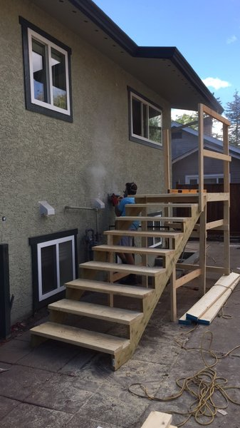 wooden stairs being built against an exterior wall