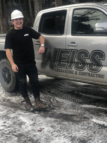 man standing next to truck with company logo